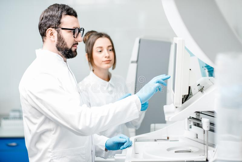 Laboratory assistants working with analizer. Laboratory assistants in unifrom working with professional medical analizer at the laboratory stock photography