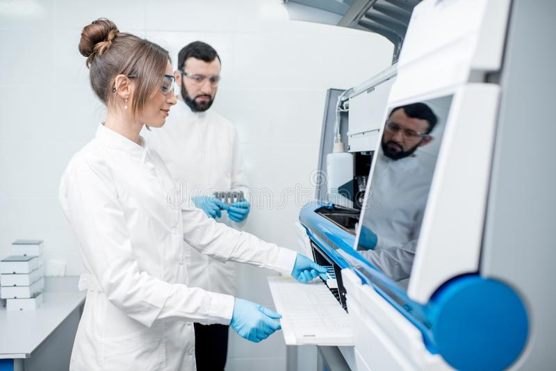 Laboratory assistants working with analizer royalty free stock images