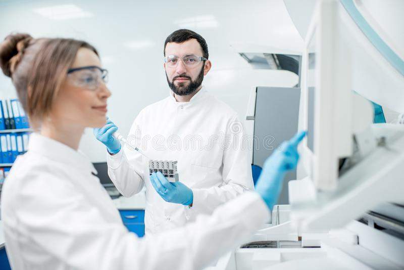 Laboratory assistants working with analizer. Laboratory assistants in unifrom working with professional medical analizer at the laboratory stock images