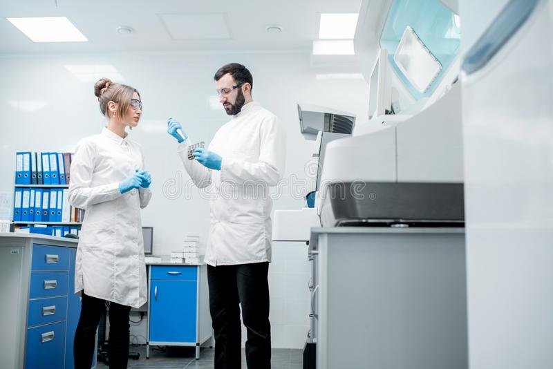 Laboratory assistants workign with test tubes stock photos