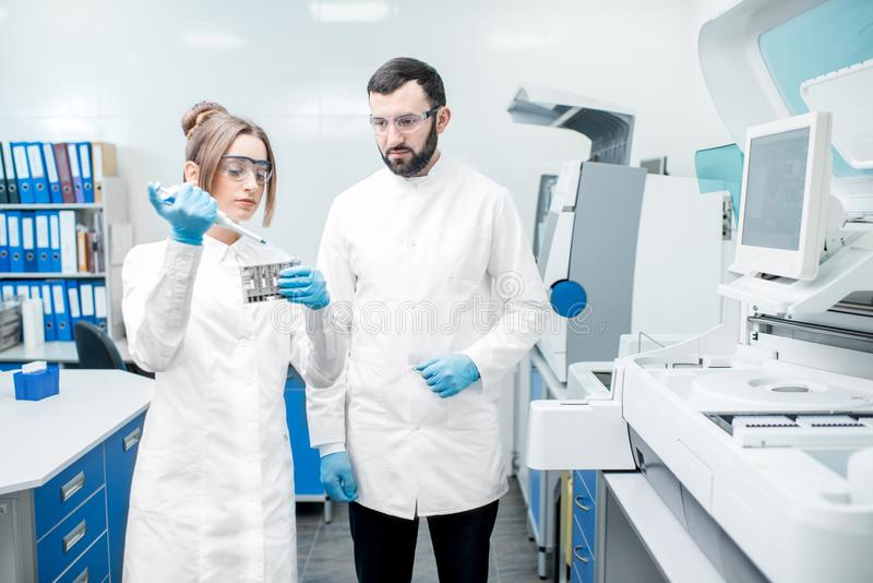 Laboratory assistants workign with test tubes. Couple of laboratory assistants in uniform working with test tubes standing near the analyzer machine in the stock photography