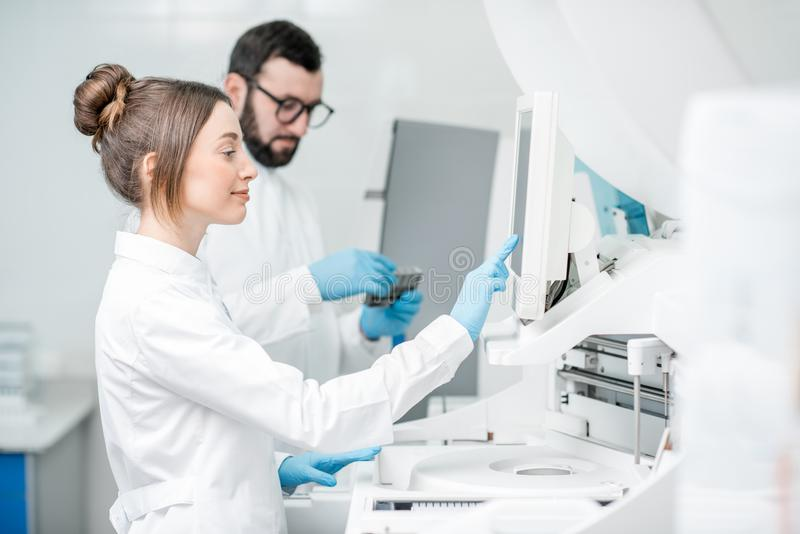 Laboratory assistants working with analizer. Laboratory assistants in unifrom working with professional medical analizer at the laboratory royalty free stock image