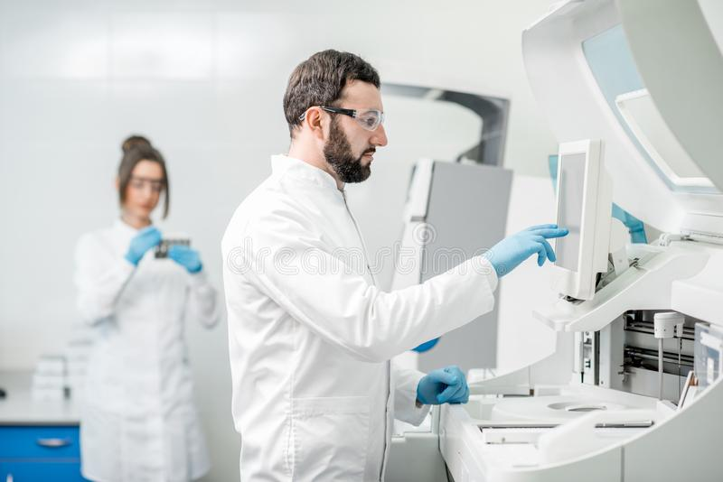 Laboratory assistants working with analizer. Laboratory assistants in unifrom working with professional medical analizer at the laboratory royalty free stock photography
