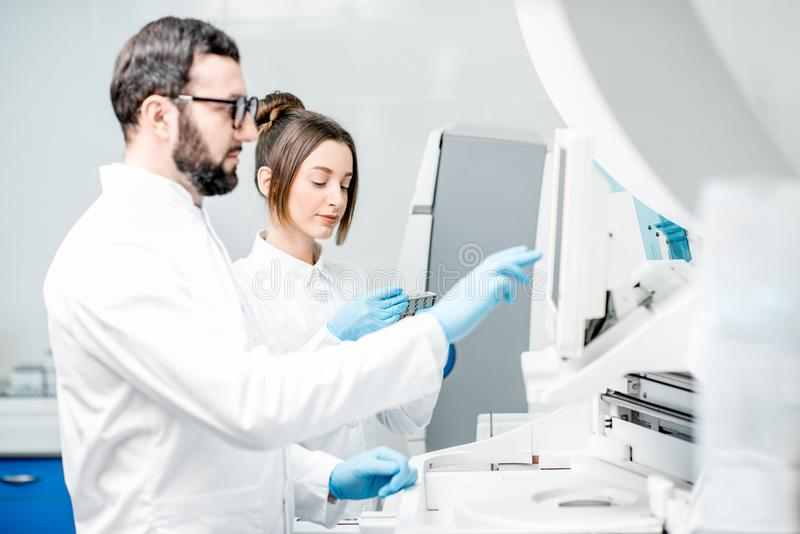 Laboratory assistants working with analizer. Laboratory assistants in unifrom working with professional medical analizer at the laboratory royalty free stock photo
