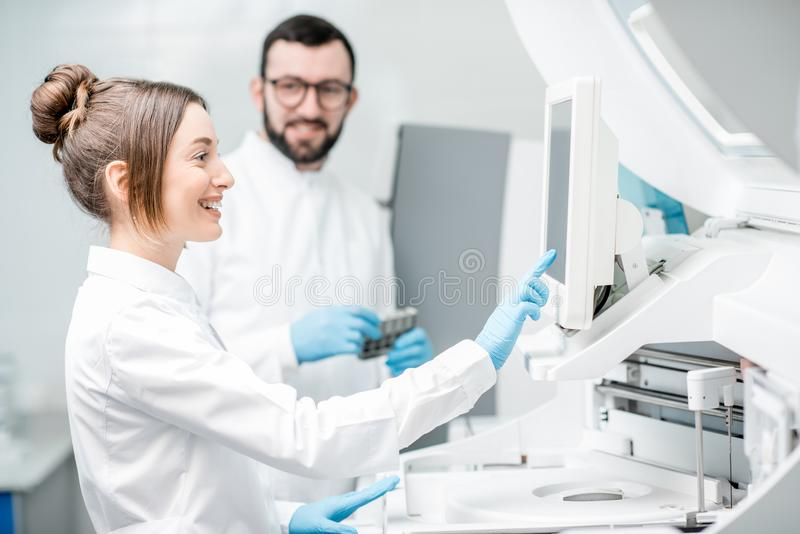Laboratory assistants working with analizer. Laboratory assistants in unifrom working with professional medical analizer at the laboratory stock photo