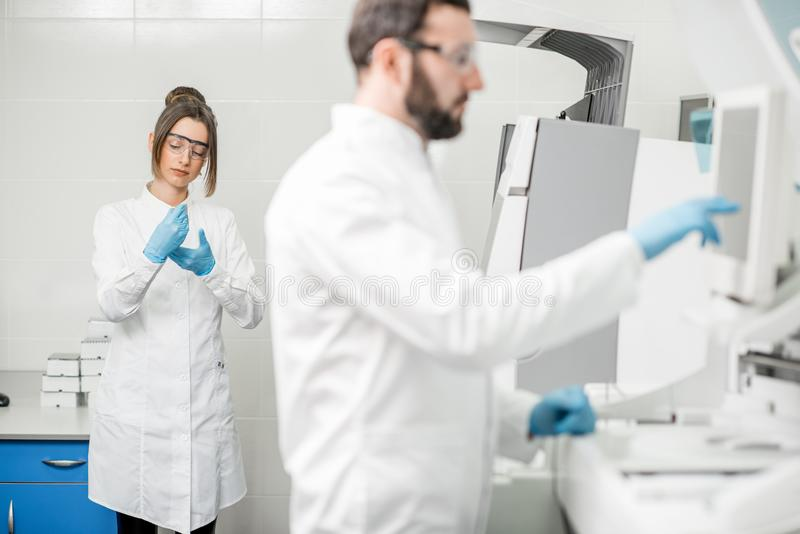 Laboratory assistants working with analizer stock photography