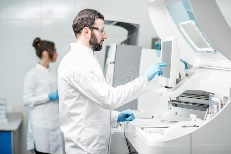 Laboratory assistants working with analizer stock photo