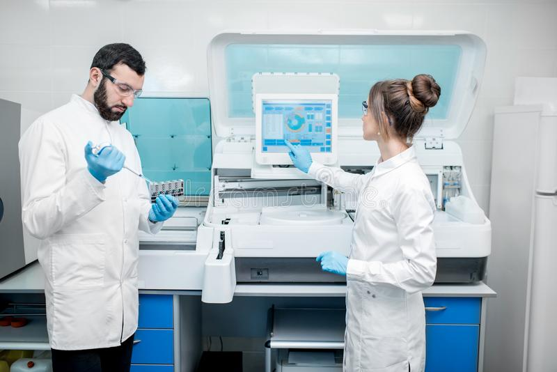 Laboratory assistants working with analizer. Laboratory assistants in unifrom working with professional medical analizer at the laboratory stock photos