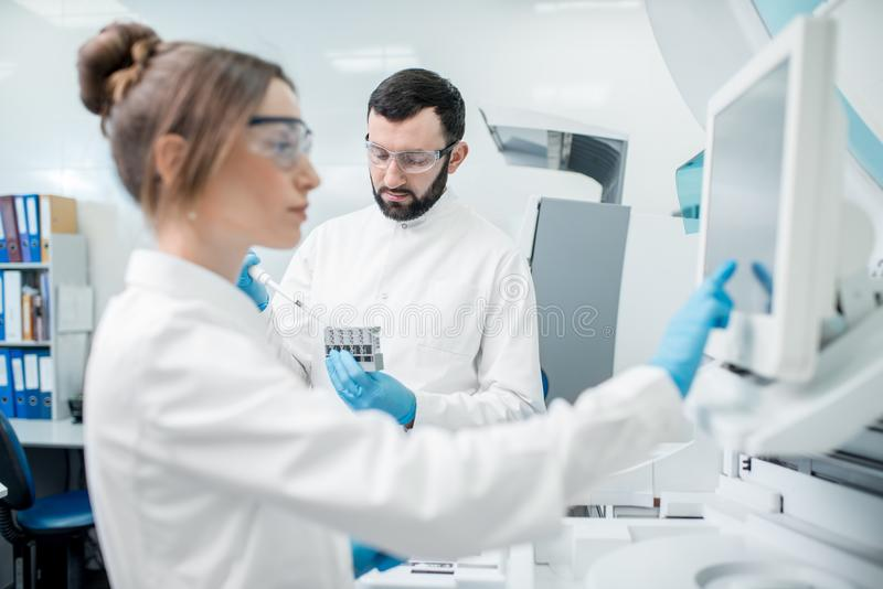 Laboratory assistants working with analizer. Laboratory assistants in unifrom working with professional medical analizer at the laboratory stock image
