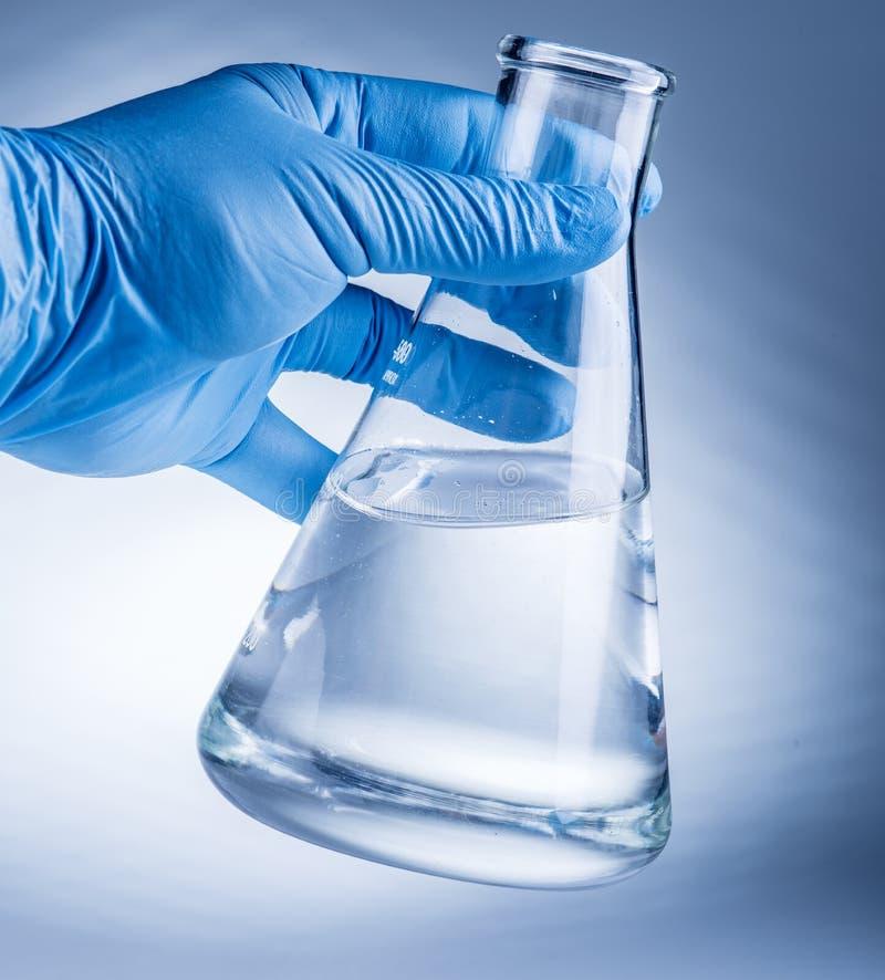 Laboratory beaker in analyst`s hand. royalty free stock photography