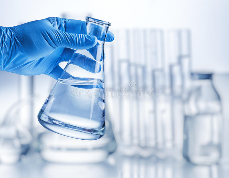 Laboratory beaker. Laboratory beaker in analyst`s hand in plastic glove stock photo