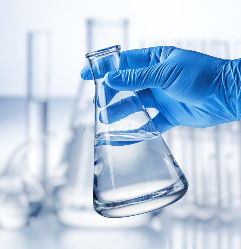 Laboratory beaker in analyst`s hand. royalty free stock images