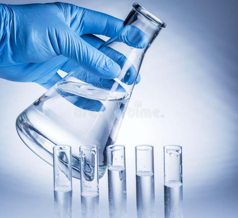 Laboratory beaker in analyst`s hand. royalty free stock photos