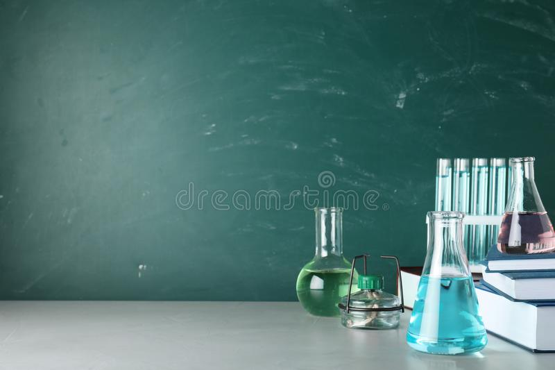 Laboratory equipment and books on table near chalkboard with space for text. Chemistry. Concept royalty free stock image