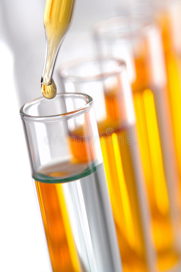 Laboratory Experiment in Science Research Lab. Laboratory pipette with drop of yellow liquid over glass test tubes for an experiment in a science research lab stock photo