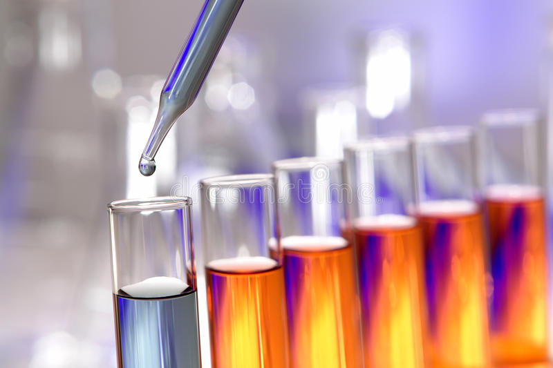 Laboratory Experiment in Science Research Lab. Laboratory pipette with drop of blue liquid over test tubes filled with orange chemical solution for an experiment royalty free stock images