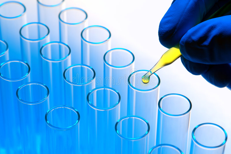 Laboratory Experiment in Science Research Lab. Scientist hand holding a laboratory glass pipette with drop of yellow liquid over test tubes for an experiment in royalty free stock images