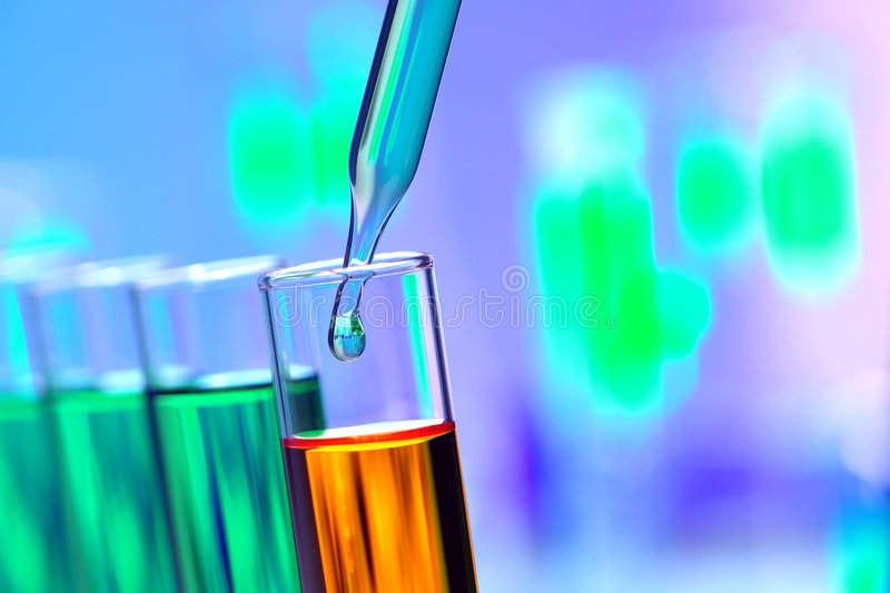 Laboratory Experiment in Science Research Lab. Laboratory pipette with drop of green liquid inside glass test tubes filled with orange chemical solution for an royalty free stock images