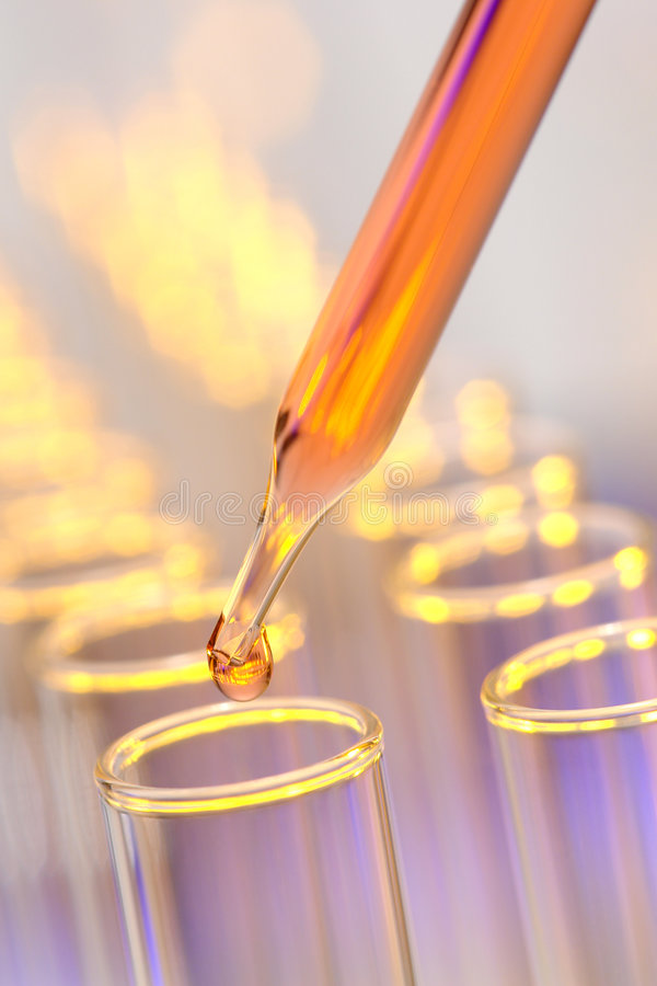 Laboratory Experiment in Science Research Lab. Laboratory pipette with orange drop of liquid over glass test tubes for an experiment in a science research lab stock image