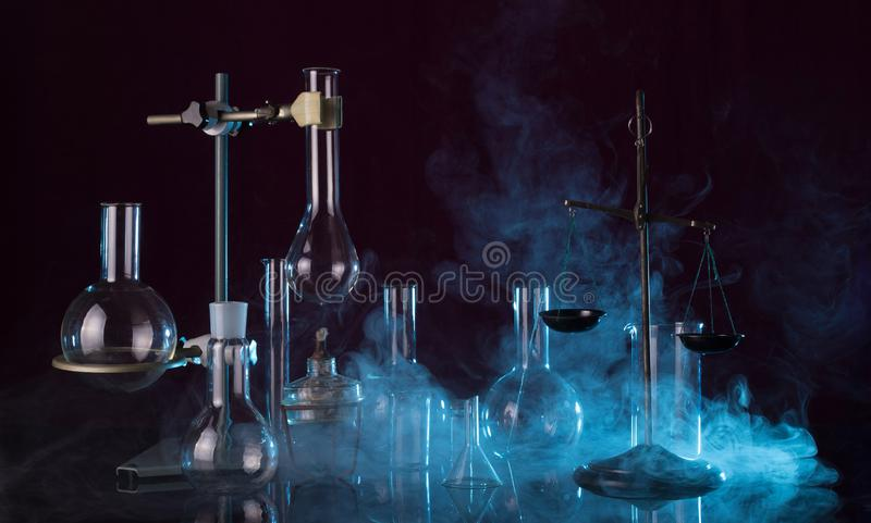 Laboratory glassware, chemical scales, tripod and a torch on dark background in the smoke royalty free stock photography