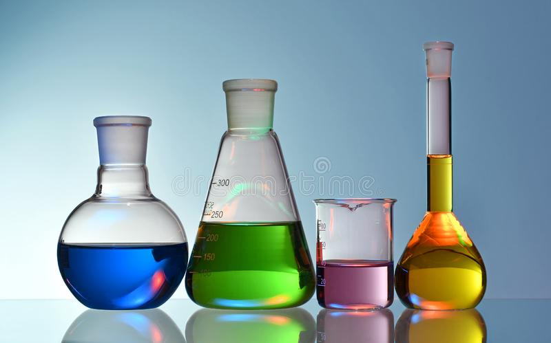 Laboratory glassware with colorful liquids on blue background royalty free stock photo