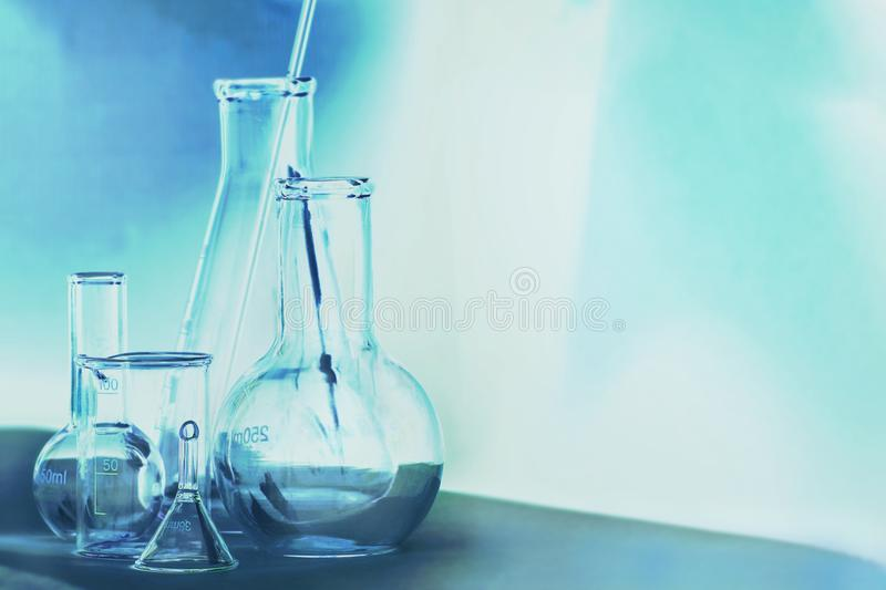 Laboratory glassware in dark blue colors and white background royalty free stock photo