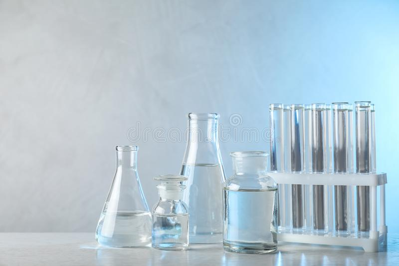Laboratory glassware with liquid samples for analysis on table against blue background. Laboratory glassware with liquid samples for analysis on table against stock photos