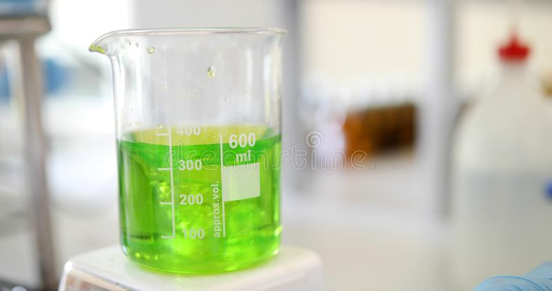 Mechanical stirring, liquid of green color is mixed in a round flask. Laboratory glassware on a stirrer. Mechanical stirring, liquid of blue color is mixed in a stock image