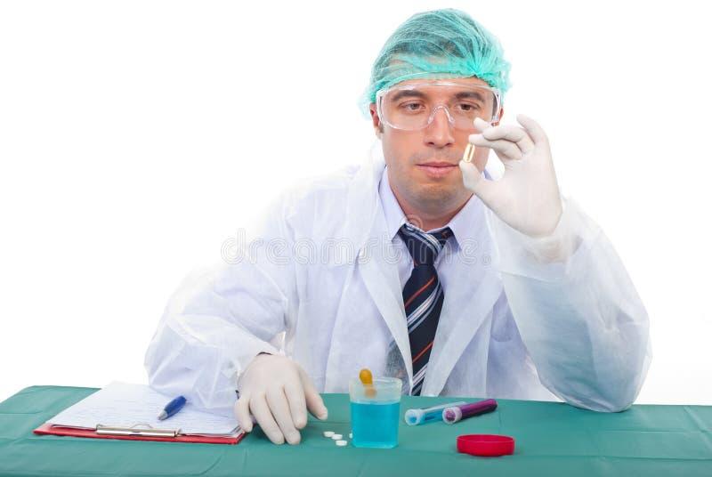 Laboratory man examine oil capsule stock photography