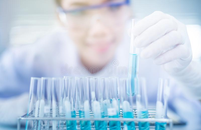 Laboratory research, dropping liquid to test tube. Professional distinguished Science specialist at work.Young Asian scientist with test tube making research in royalty free stock images