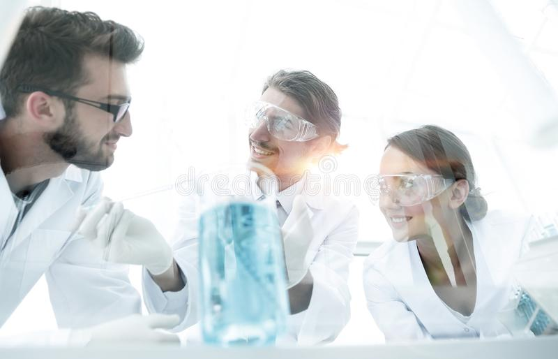 Group of scientists working on an experiment at the laboratory. Laboratory with scientist working with test tubes flask and microscope royalty free stock image