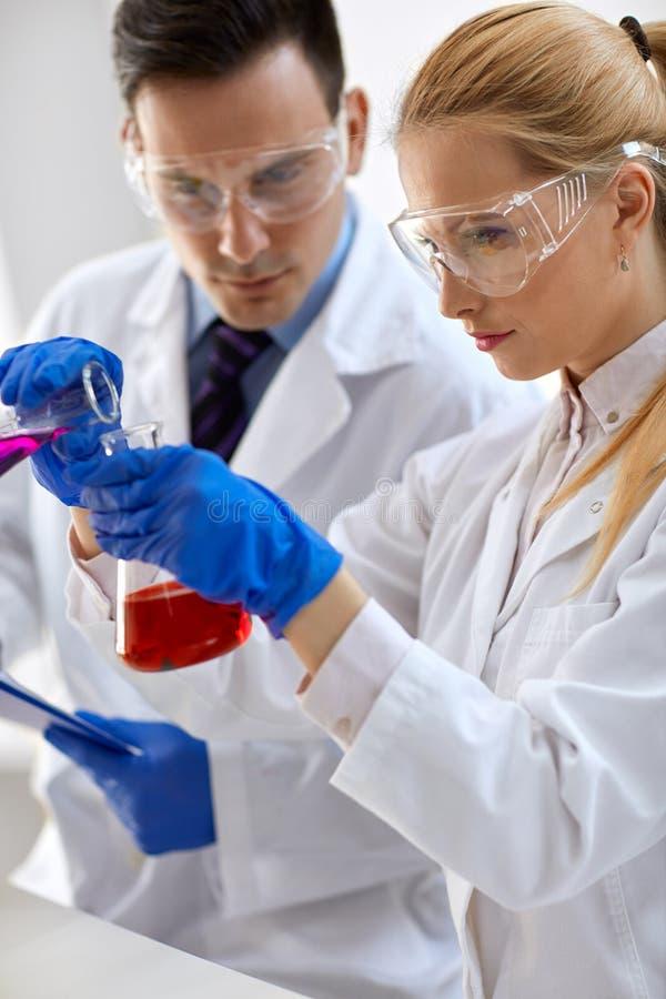 Laboratory technician doing chemistry experiment stock photography