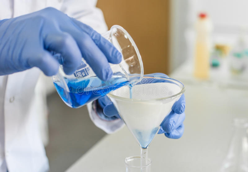 Laboratory technician performs tests and pouring blue liquid. Scientific laboratory technician performs tests and pouring blue liquid. Macro shot stock images