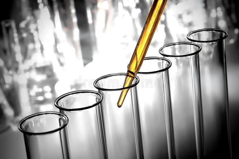 Laboratory Test Tubes in Science Research Lab. Laboratory pipette with emerging drop of yellow liquid over glass test tubes filled with chemical solution for a stock photos