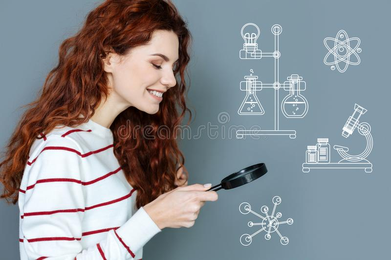 Positive laboratory worker smiling while using a magnifying glass royalty free stock photo