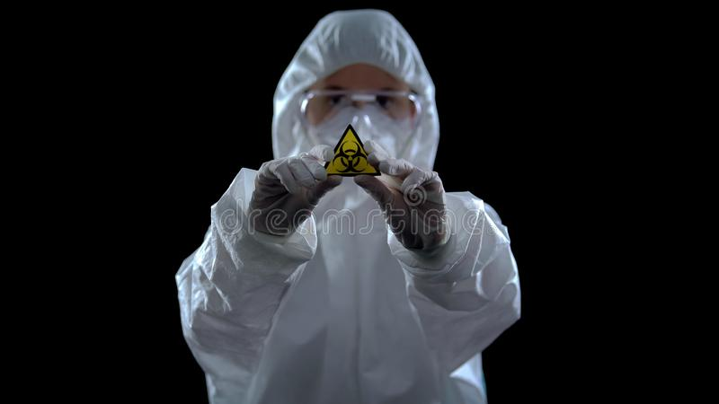 Laboratory worker in protective suit showing biological hazard symbol, weapon royalty free stock photos