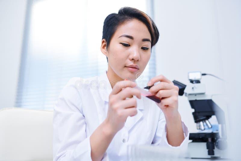 Laboratory worker writing on test tube stock image