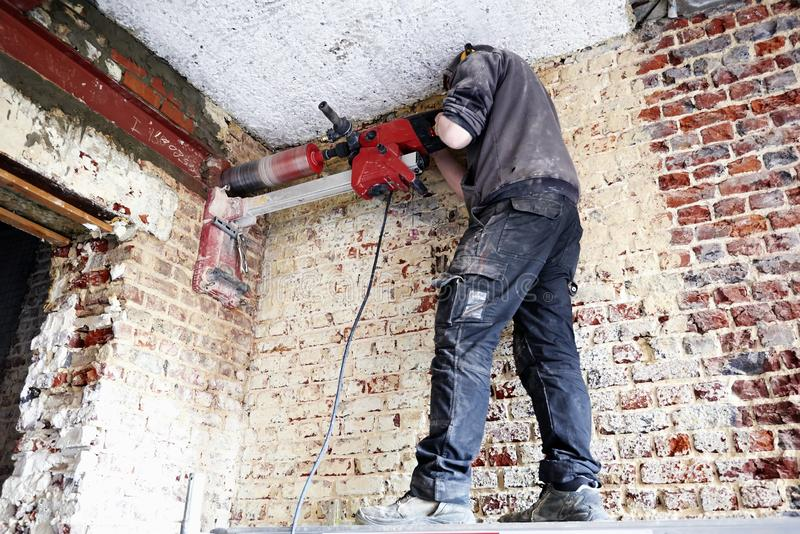 Laborer pierce a big round hole in a brick wall stock photos