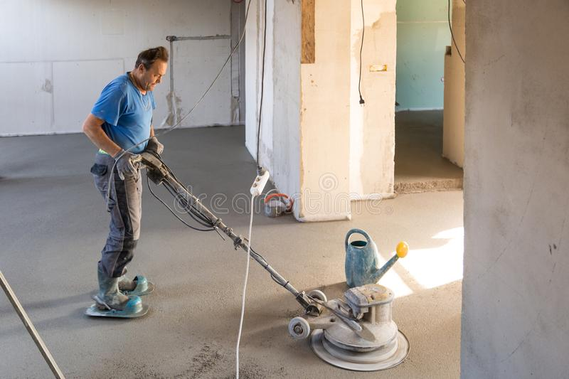 Laborer polishing sand and cement screed floor. royalty free stock photos