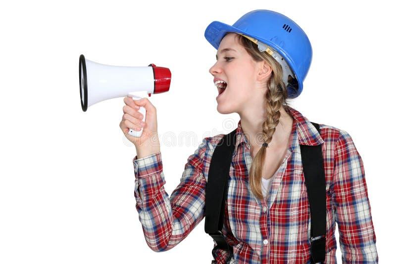 Laborer screaming in a bullhorn. Woman laborer screaming in a bullhorn stock photo
