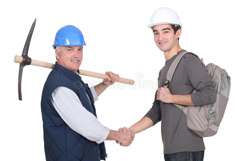 Laborer welcoming young apprentice stock photo