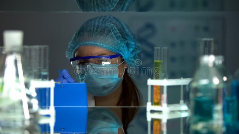 Laborforscher, der die Experimentergebnisse, arbeitend auf medizinisches Projekt schreibt lizenzfreie stockbilder