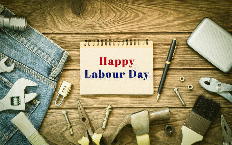 Labour day background concept - Jeans, many handy tools, notebook with happy labour day text , wooden background top view stock photos
