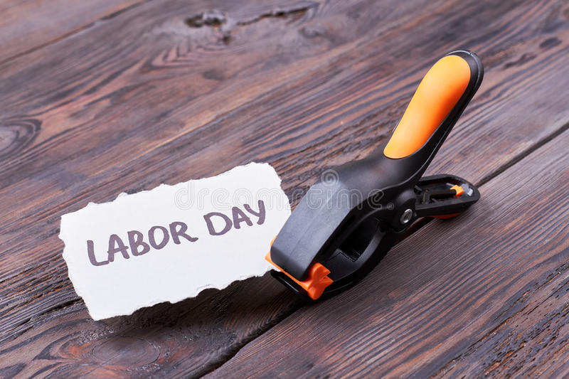 Labour Day card and clamp. Plastic clamp on wooden background. Build the atmosphere of holiday royalty free stock photos