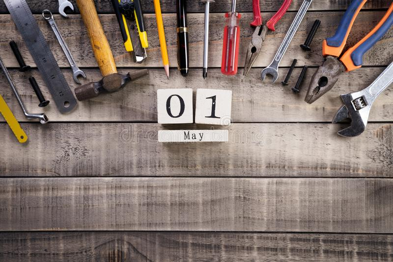 Labour Day, Wooden Block calendar with many handy tools on wooden background texture.  royalty free stock images