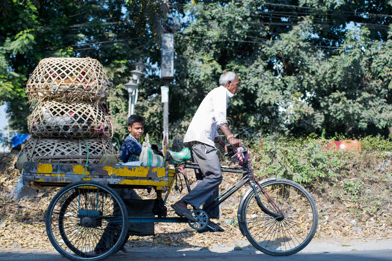 Labour in Siliguri. SILIGURI, INDIA – DECEMBER 5, 2016: three-wheeled cart is widely used for transport of produce from a wholesale market in Siliguri stock photos