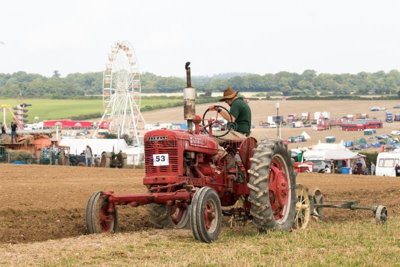 Labourage rouge de tracteur de farmall de vintage photo stock