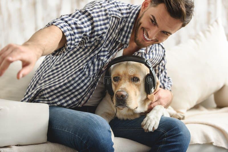 Labrador che ascolta la musica mentre il suo proprietario che gioca con lui fotografia stock