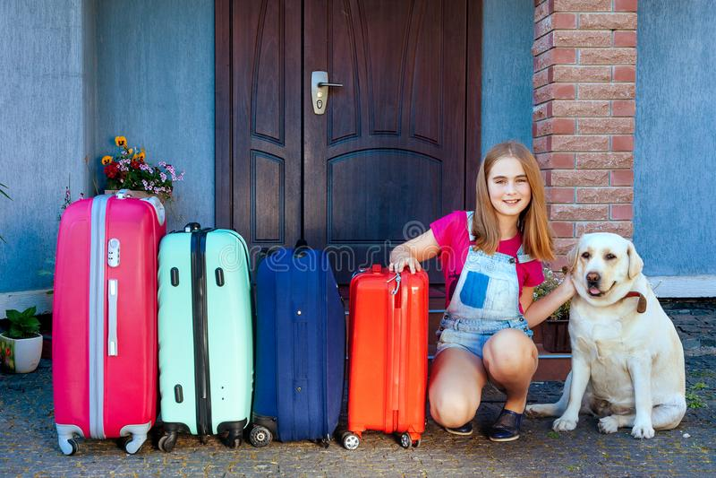 Labrador dog girl kid baggage blue pink orange house sun summer luggage family car ready holidays plant green four. A girl and a large labrador dog near multi stock photos