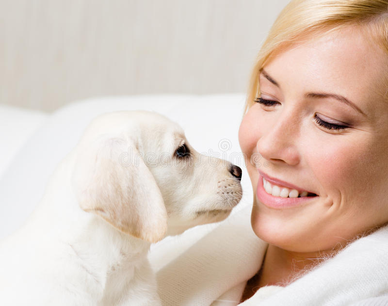 Labrador puppy and woman look at each other. White Labrador puppy and woman sitting at the white leather sofa look at each other stock image